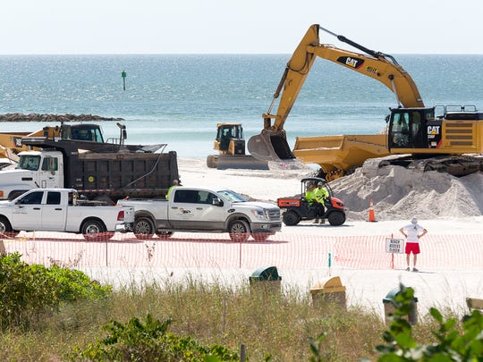 Dump trucks deliver sand from an inland mine to South Beach on Marco Island during a Collier County beach renourishment project on Wednesday, Nov. 2, 2016.