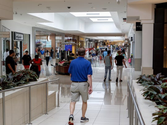 Shoppers stroll through Kenwood Towne Centre near the