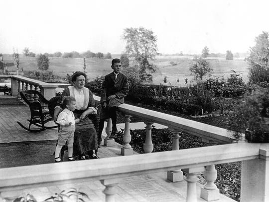 In this 1918 photograph, Eva Love Hickey McPherson (center) and her sons Frederick (left) and Robert (right) enjoy fresh air on the back balcony of the McPherson Mansion in Howell.