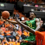 """Oregon's Elgin Cook (23) extends for the hoop as Oregon State's Daniel Gomis (14) tries to defend in the second half of the Oregon vs. Oregon State """"Civil War"""" men's basketball game in Corvallis on Wednesday, March 4, 2015. The Ducks won the game 65-62."""