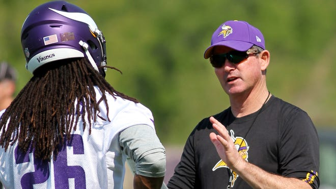 Vikings coach Mike Zimmer talks with rookie cornerback Trae Waynes on Wednesday.