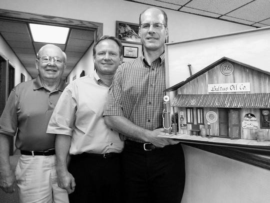 Vern Baltus, far left, poses with his sons, John, center, and Frank at the Baltus corporate offices in Marshfield with a piece of art representing their business. Vern Baltus has since passed away.