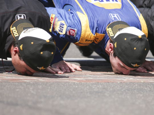 Alexander Rossi (middle), kisses the bricks with team