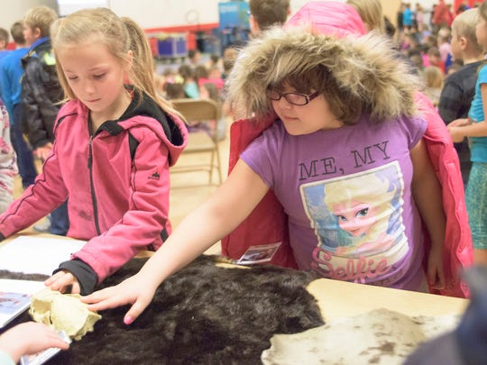 Autumn Smiley, left and Autumn Brasseur feel a sea otter pelt during The Oregon Coast Aquarium's education tour at Aumsville Elementary School.
