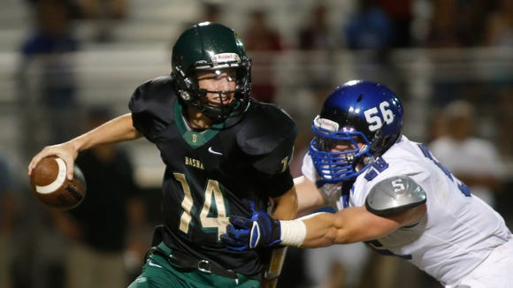 Basha QB Ryan Kelley tries to fight off Chandler #56 DL Kyle Hunt during a high school football game at Basha High in Chandler, AZ on October 24, 2014.