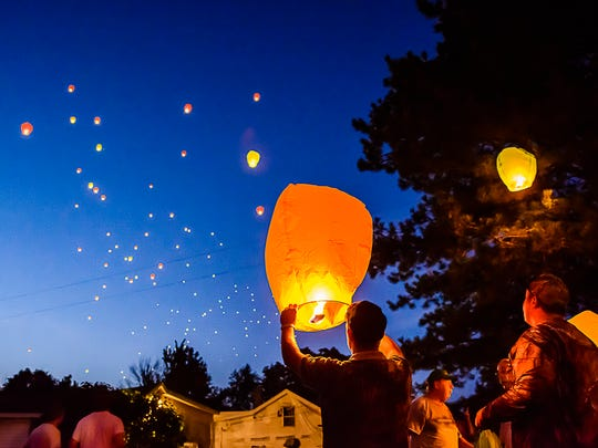 A person attending a vigil for Paige Cords that was killed in a car crash on lets a floating lantern join others already in the sky, Thursday  in Bellevue.