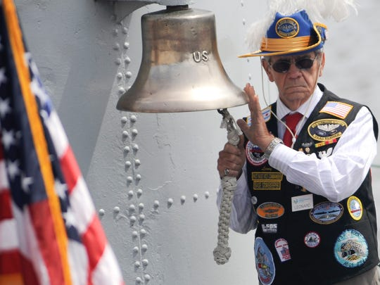 File - Lenny Kleinmark rings the bell aboard the USS