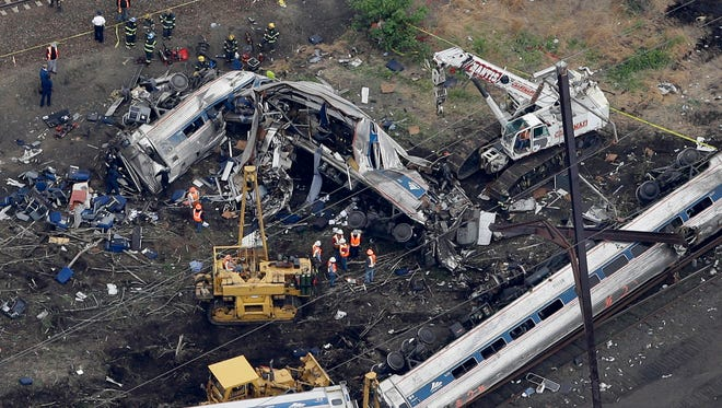 Emergency personnel work at the scene of a deadly Amtrak train wreck in Philadelphia on May 13, the day after the crash.