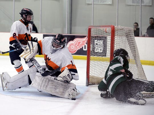Northville goalie Owen Moruzi (1) makes the pad save on Novi's Eric Budd (right), while Noah Eckerle (8) also converges on the net.