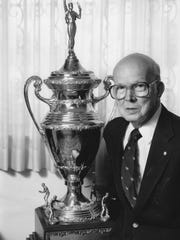 Jimmy McClure in 1990 with his 1939 United States table tennis trophy.