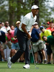 Tiger Woods watches his shot on the fourth hole during