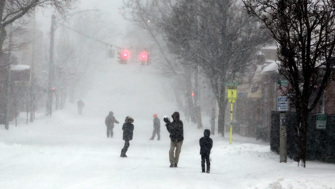 Christopher Clay has a snow ball fight with his sons Christian, 8, and Alexander, 11, as they walk on Main St. in Beacon March 14, 2017. The three were out looking in vain for an open restaurant for breakfast. The late winter storm is expected to drop up to two feet of snow on the region throughout the day.