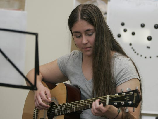 Alisa Pavlovsky of Manalapan plays guitar playing during a lesson with John Spoulos, a private music instructor, at Freehold Music Center, Freehold Township.