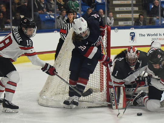 Team USA's Hannah Brandt (20) fights for the puck in