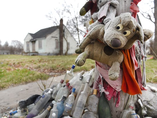 Makeshift memorials with weathered stuffed animals and red bandanas dangling from utility poles in the east side Detroit area.