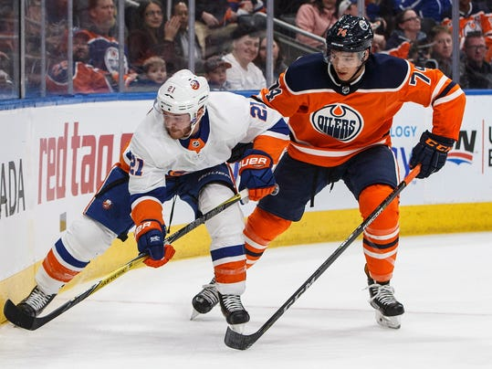 New York Islanders' Chris Wagner (21) and Edmonton Oilers' Ethan Bear (74) compete for the puck during the third period of an NHL hockey game Thursday, March 8, 2018, in Edmonton, Alberta. (Jason Franson/The Canadian Press via AP)