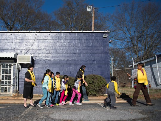 Pastor Martha Evans leads students to the classroom