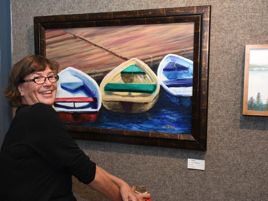 "Tara O'Neill with her painting ""Resting."" The Marco Island Center for the Arts hosted their ""Second Tuesday"" reception for the exhibit titled ""Oh the Places You Have Been,"" postponed from September by Hurricane Irma."