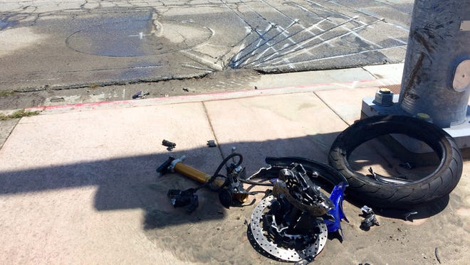 Mangled parts of a motorcycle are seen on Gene Autry Trail, where a motorcyclist died in a collision Monday.