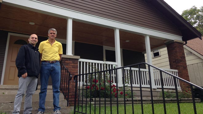 Pastor Andrew Draper, left, and Keith Miller stand in front of a rehabilitated house at 204 E. Seventh St. in Muncie.