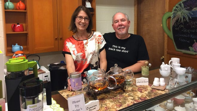 Livonia residents Colleen and Pat Cannon, who visited China in May, offered Chinese tea samples Aug. 23 at her Plymouth TranquiliTea shop. She got the top she's wearing at a Chinese silk store.