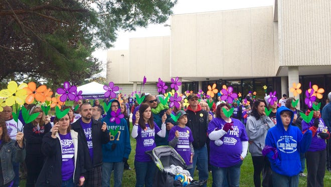 Each participant received a colored flower that designates how Alzheimer's disease has impacted them or their family. Blue flowers are given to those individuals living with the disease; purple flowers are given to those who have lost someone to the disease; yellow flowers are given to caregiver; and orange flowers represent individuals who are advocating for a world without Alzheimer's.