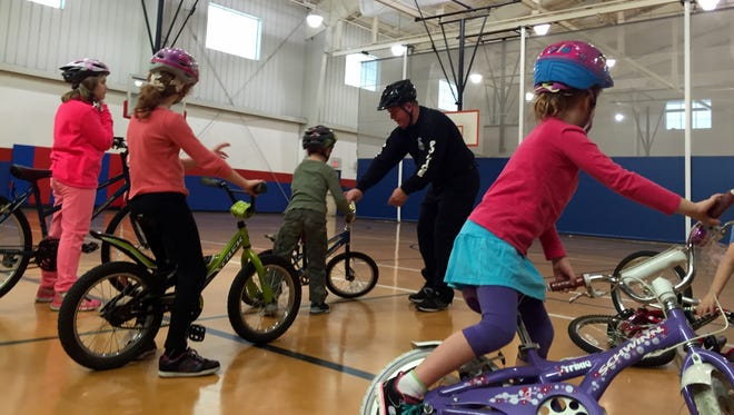 """Master Corporal Brian Whitte leads lessons at the Wilmington Police Athletic League's """"How to Ride a Bike"""" program."""