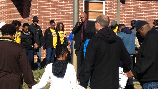 Supporters of keeping West Middle School open prayed Saturday around the flagpole in front of the school.