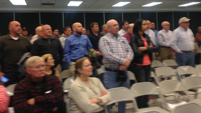 Audience members stand in support of the poultry industry at a public hearing on Wednesday, Feb. 3, 2016 in Parksley, Virginia.