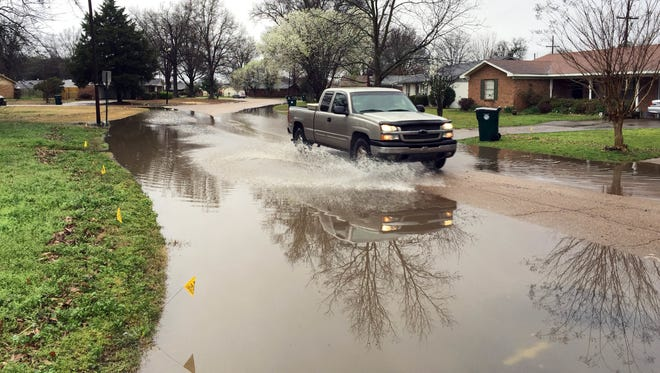 In this photograph taken March 10, 2016, a pickup truck makes its way through high water along Medallion Drive in Greenwood, Miss., during a break from an almost constant rain since Wednesday. Flooding is expected to continue in the Delta as additional rains are expected through Saturday.