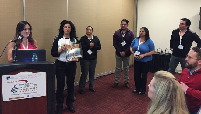Lorraine Sanchez, Lydia Macklin and La Clinica de Familia staff receive the Champion Award at the state conference of the New Mexico Alliance for School Based Health Care in Albuquerque.