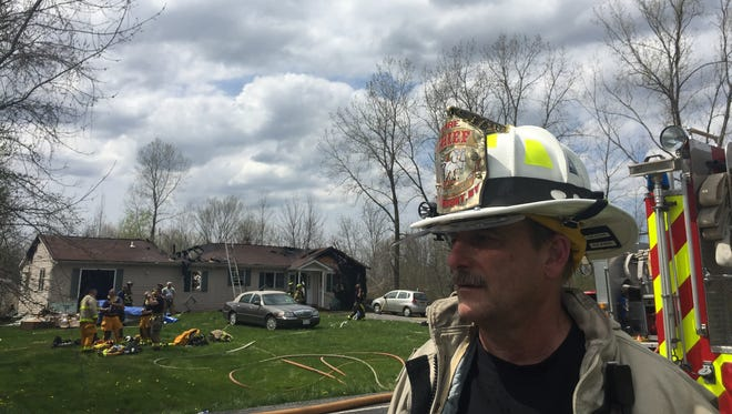 Brockport Fire District chief Mike LaDue stands in front of the home at 2999 Redman Road in Clarkson that was burned by fire May 12.