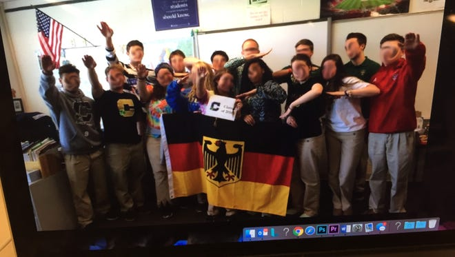 Screen shot of photo captured in World Language classroom at Cathedral High School showing students raising their arms in a Nazi salute.