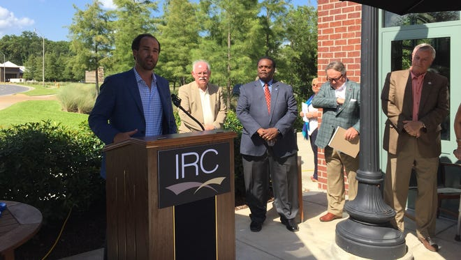 Jared Walker, vice president of IRC, talks about the hotel renovation business Tuesday at a ribbon cutting for its new Tower Drive office.