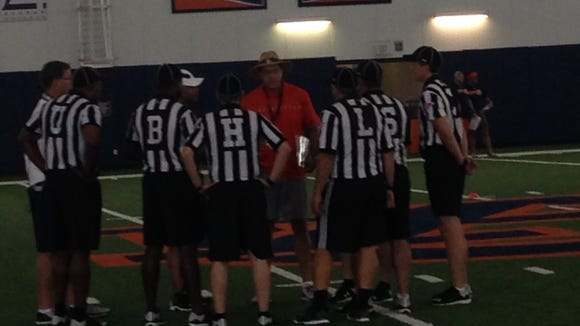 Auburn head coach Gus Malzahn going over procedures with referees for the team's fourth preseason practice.