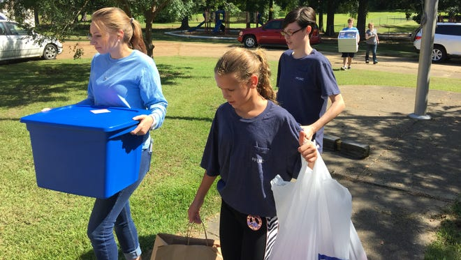 Club Kid President Karlee Littleton (left) and Pineville FUMC youth Nell White (back) and Ally Clear deliver uniforms.