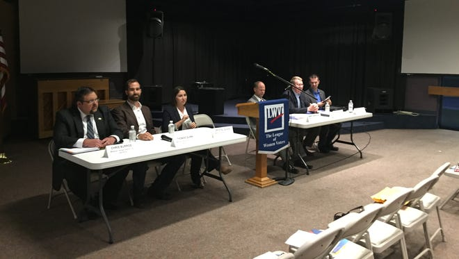 Candidates for District 132 and District 135 sit on the left and right side, respectively, of a podium Thursday, Nov. 3, 2016, at First Baptist Church. From left, they are Libertarian Chris Burros, Republican Thomas Quinn, Democrat Crystal Quade, Democrat Randy Alberhasky, Republican Steve Helms and Libertarian David Carr.