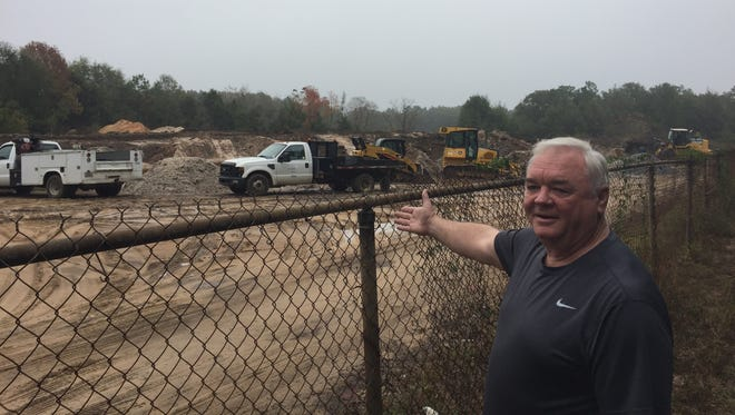Jerry Holtzworth, a resident of the Hidden Oaks neighborhood, points at the mystery soil transported to a site near his residence south of the airport.