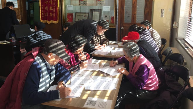 A group of senior citizens write their wills at a free legal center in Beijing.