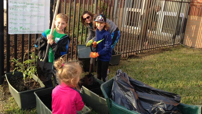J.D. Parker current (Natalie and Aiden) and future (Julianna) students and parent (Vikki) add soil to earth boxes at J.D. Parker's Green Club Farm to School Garden workday.