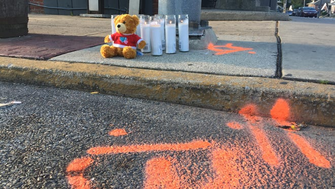 A stuffed teddy bear, candles and police spray paint mark the spot where a woman was fatally shot in York on Tuesday. Police have said they believe she was an innocent victim.