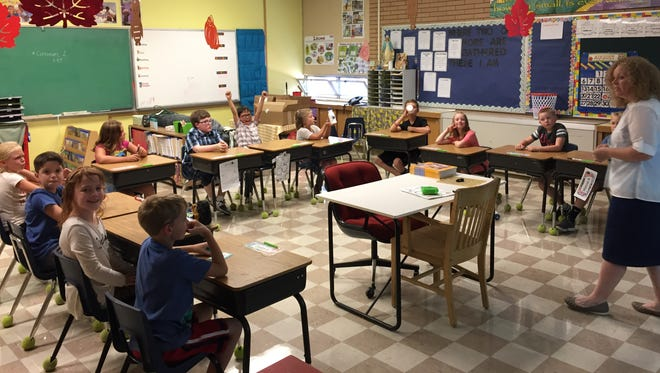 Erin Voeller's third grade class practices sitting at their desks on the first day of school at Holy Spirit Catholic School.