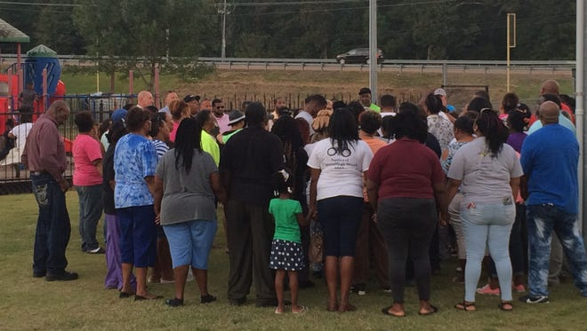 About 100 people gather around the family of James Perry for prayer after the vigil in his honor on Thursday night at West Park in Bolivar.