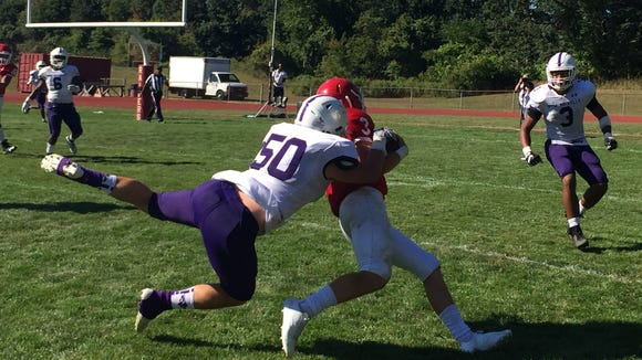 New Rochelle's Aidan Lilly makes a tackle in a 48-0