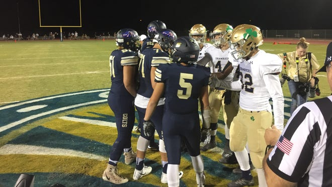 Players from Queen Creek Casteel and Yuma Catholic meet at midfield before their game.