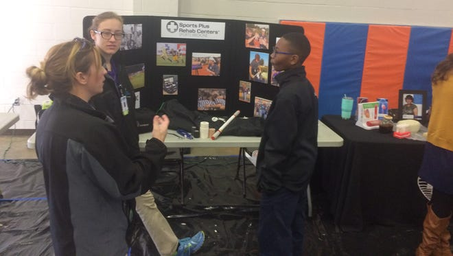 SportsPlus Physical Therapy representatives Leigh Ann Gaines and Celia Teel talk about their job with Northeast Middle student Chase Smith.