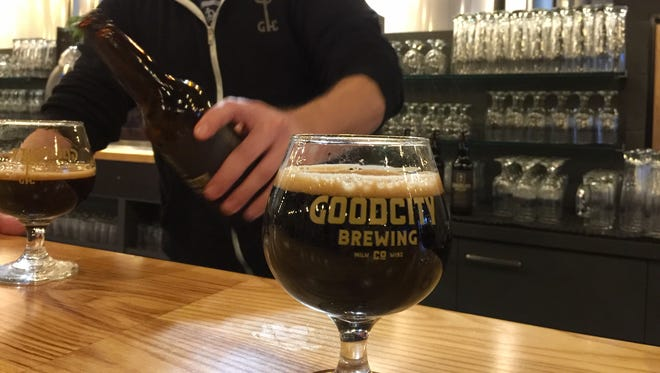 Good City co-founder and brewmaster Andy Jones pours samples of the brewery's bourbon barrel-aged Density.