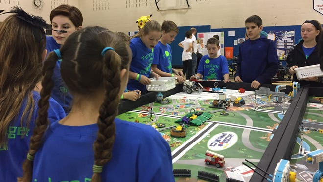 Bella Flores, Ryan Blum, Jake Byrd, Meryl Haller, Sam Byrd, Will Fleck, Avery Brown and Emma Powers get their robot prepared and ready to go to compete in the mission portion of Grandview Heights First Lego League tournament recently.