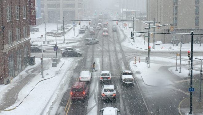 Heavy snow falls on motorists as they make their way north on Delaware Street out in front of Bankers Life Fieldhouse in Downtown Indianapolis on Saturday, March 24, 2018.