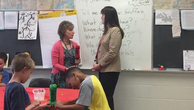 Candice McQueen (right) talks to a teacher during her visit to Bartlett Elementary. She observed classrooms to see Read to be Ready Summer camps.